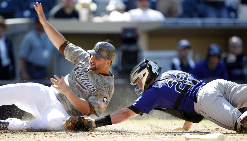 Photo -   San Diego Padres' Yonder Alonso, left, scores ahead of the tag by Colorado Rockies catcher Jordan Pacheco (22) on a single by Padres' John Baker during the first inning of their baseball game in San Diego, Sunday, Sept. 16, 2012. (AP Photo/Alex Gallardo)