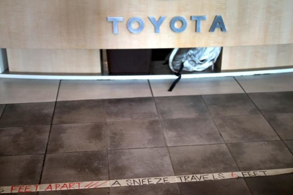 Photo -  Social distancing is marked at the counter at Fowler Toyota in Norman. [Doug Hoke/The Oklahoman]