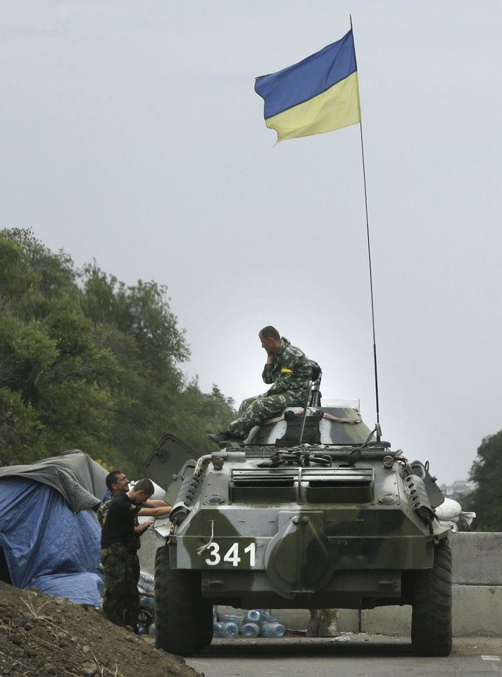 Photo - Ukrainian forces guard  a checkpoint in the town of Mariupol, eastern Ukraine, Thursday, Aug. 28, 2014. Ukraine's president Petro Poroshenko called an emergency meeting of the nation's security council and canceled a foreign trip Thursday, declaring that