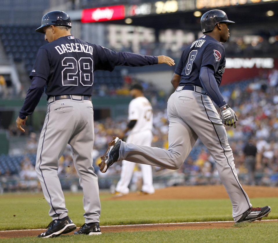 Photo - Atlanta Braves' Justin Upton heads home after being greeted by third base coach Doug Dascenzo on hitting a three-run home run off Pittsburgh Pirates starting pitcher Francisco Liriano in the third inning of the baseball game on Tuesday, Aug. 19, 2014, in Pittsburgh. (AP Photo/Keith Srakocic)