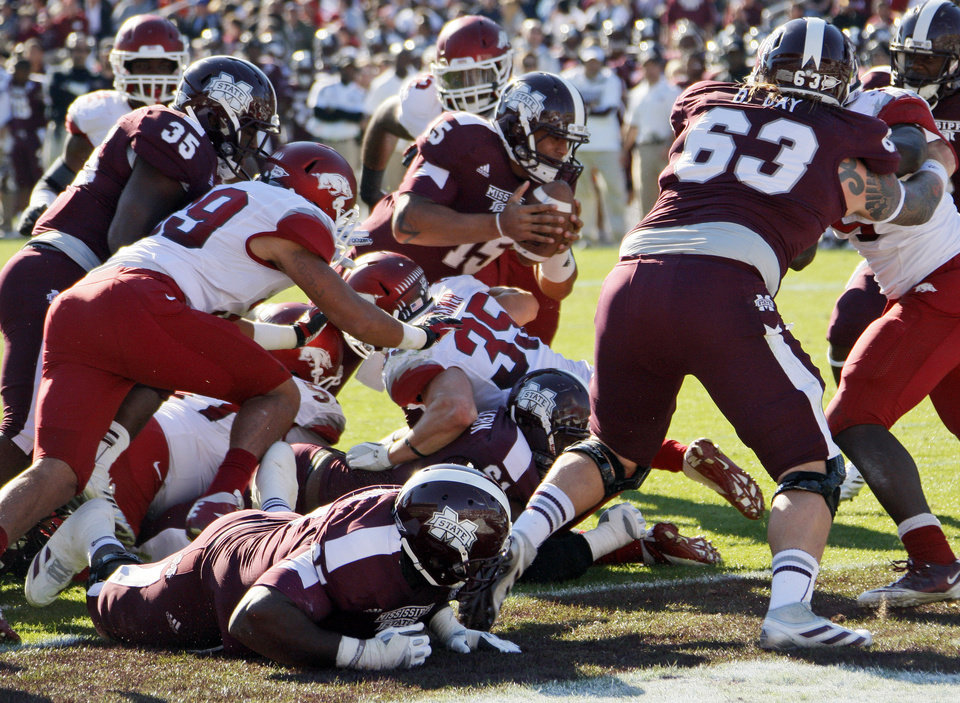 Photo -   Mississippi State quarterback Dak Prescott (15) pushes through Arkansas defenders including linebacker Jarrett Lake (39) and safety Ross Rasner (35) for a touchdown in the third quarter of an NCAA college football game in Starkville, Miss., Saturday, Nov. 17, 2012. Mississippi State won 45-14. (AP Photo/Rogelio V. Solis)