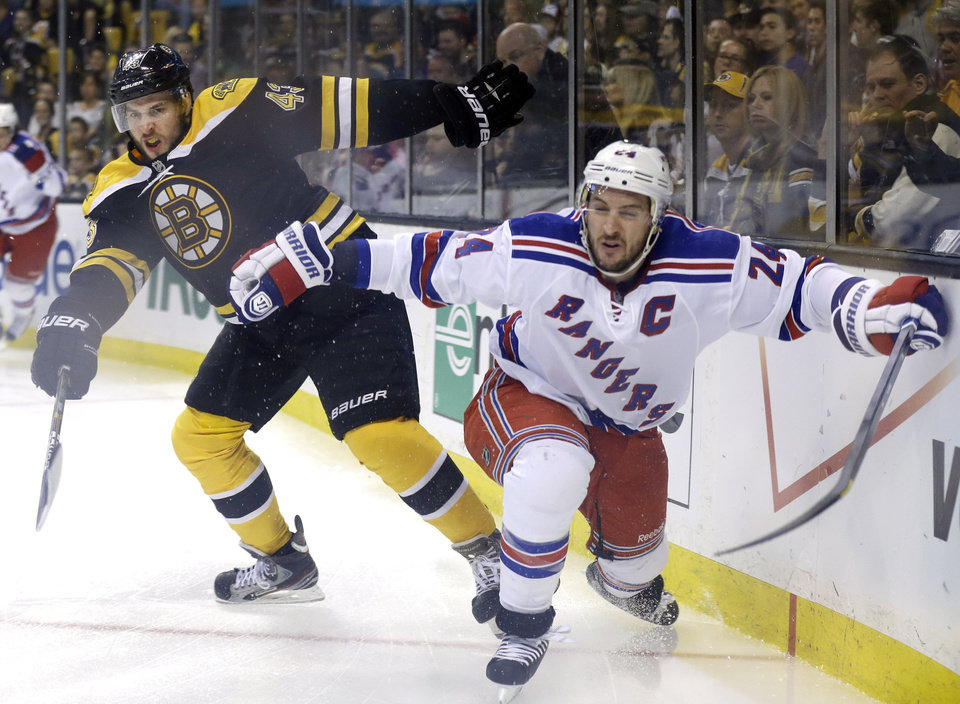 Photo - Boston Bruins defenseman Matt Bartkowski (43) and New York Rangers right wing Ryan Callahan (24) grapple along the boards during the first period in Game 2 of the NHL Eastern Conference semifinal hockey playoff series in Boston, Sunday, May 19, 2013. (AP Photo/Elise Amendola)