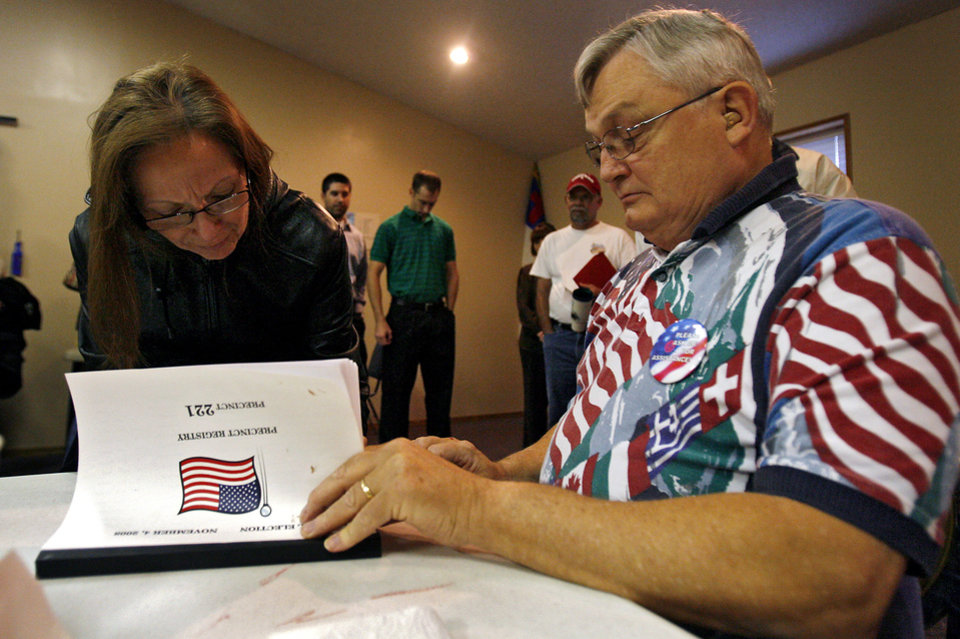 Photo - Polling volunteer George Hoebing signs in voter Stella Sifuentes during the Presidential election polling location at Canadian Hills Church of the Nazarene on Tuesday, Nov. 4, 2008, in Yukon, Okla.   BY CHRIS LANDSBERGER, THE OKLAHOMAN
