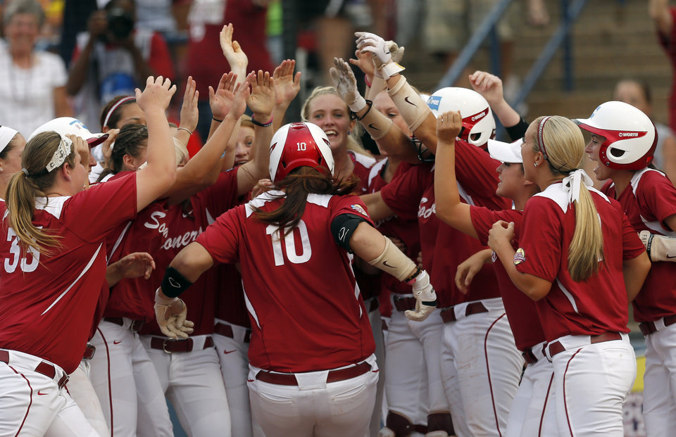 Photo - Oklahoma celebrates a Oklahoma's Keilani Ricketts (10) home run during the third inning of Women's College World Series softball game between Oklahoma and Tennessee at ASA Hall of Fame Stadium in Oklahoma City, Tuesday, June, 4, 2013. Photo by Sarah Phipps, The Oklahoman