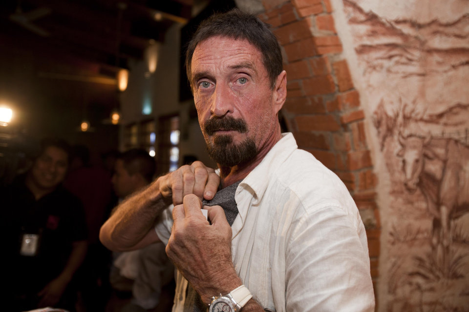 Photo - Software company founder John McAfee adjusts a microphone in preparation for an interview in Guatemala City, Tuesday, Dec. 4, 2012.  McAfee, 67, has been identified as a
