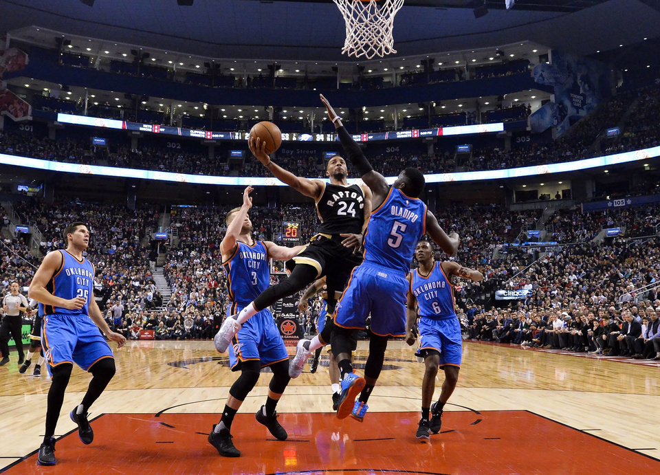 Photo - Toronto Raptors guard Norman Powell (24) drives between Oklahoma City Thunder guard Victor Oladipo (5) and forward Domantas Sabonis (3) during the first half of an NBA basketball game Thursday, March 16, 2017, in Toronto. (Nathan Denette/The Canadian Press via AP)