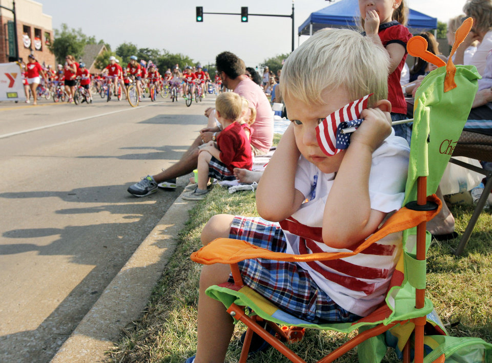 Three year old Konnor Fischer holds his ears to muffle the sound of motorcycles during the annual LibertyFest Fourth of July Parade in downtown Edmond, OK, Thursday, July 4, 2013, Photo by Paul Hellstern, The Oklahoman