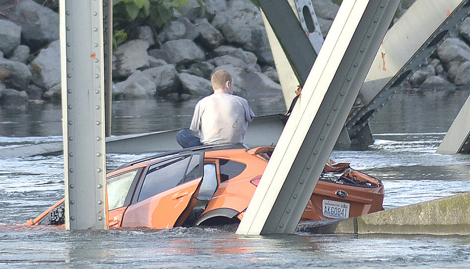Photo - An unidentified man waits on his submerged vehicle in the Skagit River Thursday May 23, 2012. The Interstate 5 bridge over the Skagit river collapsed north of Seattle Thursday evening, dumping two vehicles into the water and sparking a rescue effort by boats and divers as three injured people were pulled from the chilly waterway. (AP Photo/Skagit Valley Herald, Frank Varga)