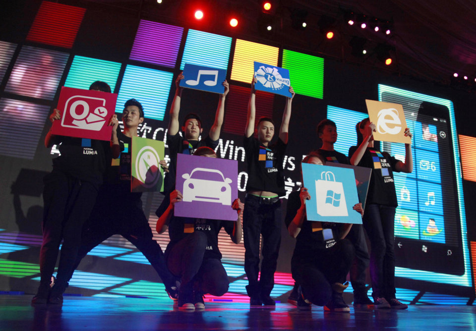 Photo - In this March 28, 2012 photo, Chinese performers hold up cards showing the various apps available for online users for shopping and other services at the launch of a mobile phone in Beijing, China. Alibaba, the e-commerce giant planning a blockbuster share sale in the U.S., shook up China's vast but sleepy retailing industry by popularizing online shopping a decade ago. Now it and China's other Internet giants are mounting challenges in areas from banking to broadcasting as smartphones bring even more people online. (AP Photo/Ng Han Guan)