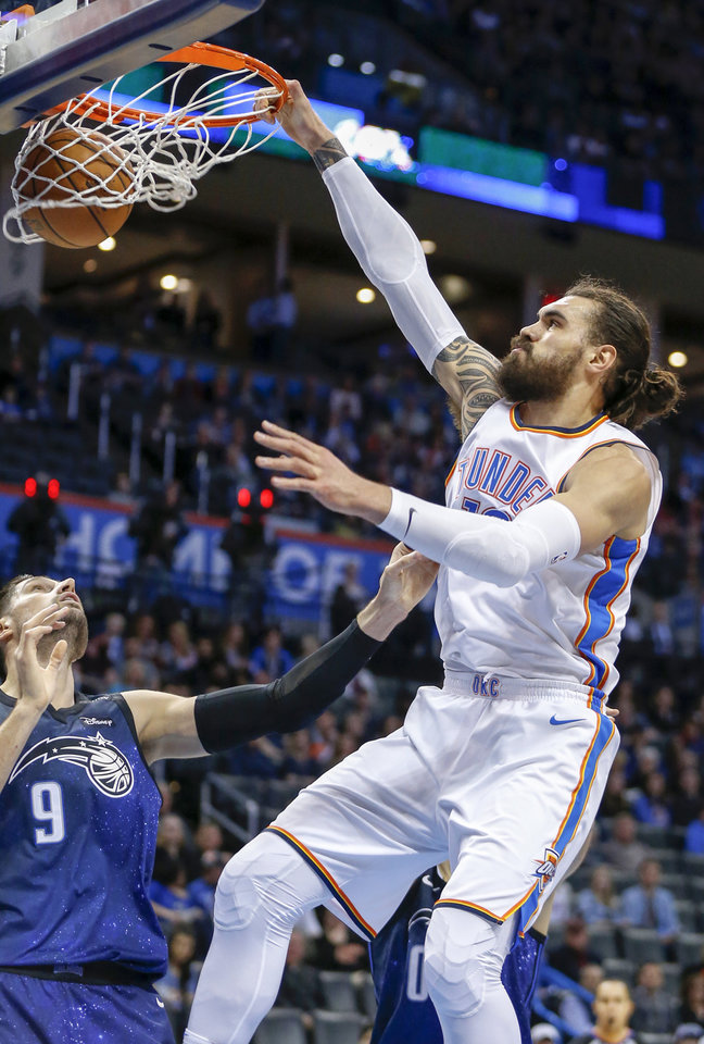 Photo - Oklahoma City's Steven Adams (12) dunks over Orlando's Nikola Vucevic (9) during an NBA basketball game between the Oklahoma City Thunder and the Orlando Magic at Chesapeake Energy Arena in Oklahoma City, Monday, Feb. 26, 2018. Photo by Nate Billings, The Oklahoman