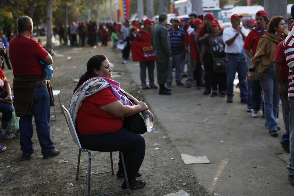 Photo - Andreina Pena rests on a chair as she waits in a line to see the body of Venezuela's late President Hugo Chavez outside the military academy where he is lying in state in Caracas, Venezuela on Saturday, March 9, 2013. Chavez died on March 5, 2013 after a nearly two-year bout with cancer. He was 58. (AP Photo/Rodrigo Abd)
