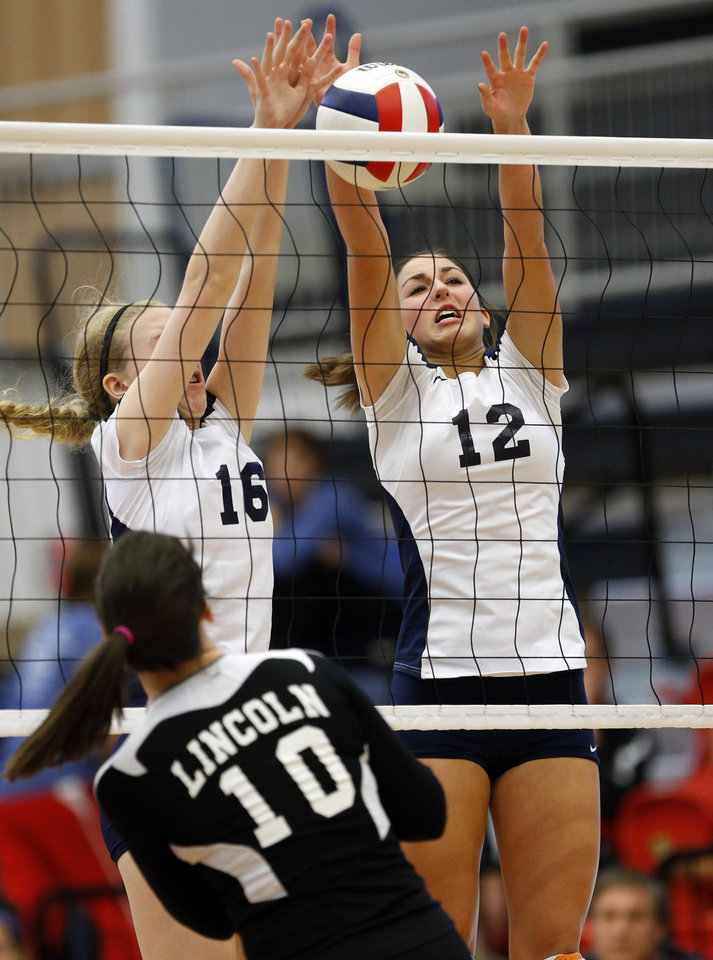 Heritage Hall's Lindsey Grace (12) and Rachel Moore (16) try to block a return by  Lincoln Christian's Maria Mathews during the Class 5A State Championship volleyball tournament on Friday, Oct. 12, 2012, in Moore, Okla.  Photo by Steve Sisney, The Oklahoman