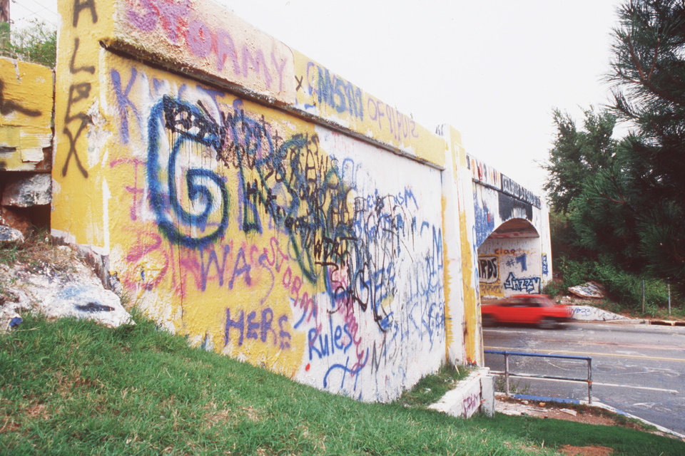 Photo - Spray-painted with colorful messages in vivid hues, the historic Graffiti Bridge in northwest Oklahoma City was reduced to fragments in 1991. oklahoman archive photo by doug hoke