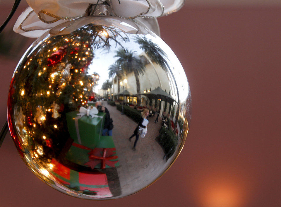 Photo - In this Thursday, Dec. 20, 2012, photo, a holiday shoppers reflected in a ornament handing from a large Christmas tree at Fashion Island shopping center in Newport Beach, Calif. Thursday, Dec. 20, 2012. U.S. holiday retail sales this year are the weakest since 2008, after a shopping season disrupted by storms and rising uncertainty among consumers.  A report out Tuesday that tracks spending, called MasterCard Advisors SpendingPulse, says holiday sales increased 0.7 percent. Analysts had expected sales to grow 3 to 4 percent. (AP Photo/Chris Carlson)