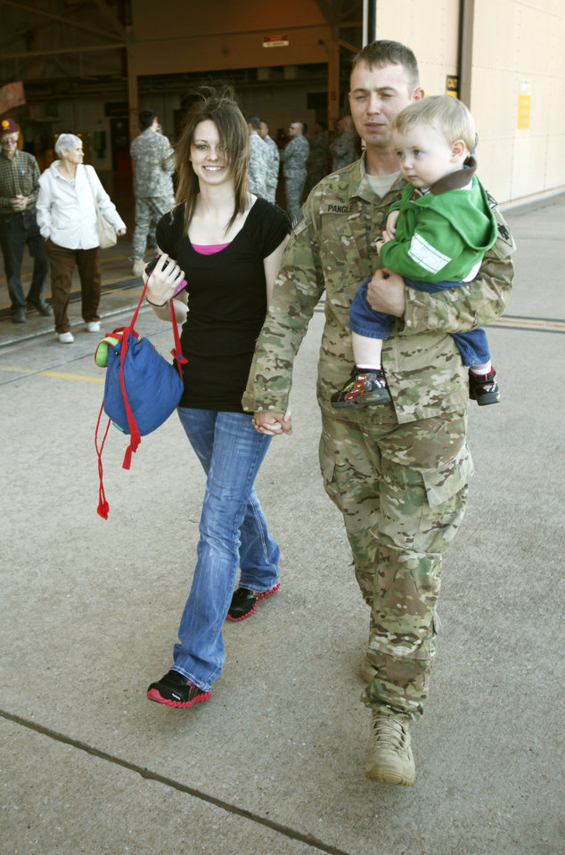 Photo - Spc. Joshua Pangle walks with his wife Meggan and 18 mionth old son Bryce after Oklahoma National Guard soldiers returned from Afghanistan to a welcome home ceremony in Oklahoma City, OK, Tuesday, March 13, 2012,  By Paul Hellstern, The Oklahoman