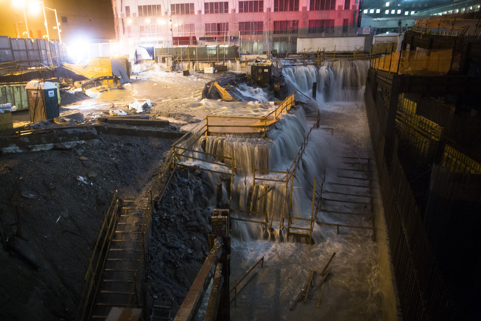 Photo - FILE - In this Oct. 29, 2012 file photo, sea water floods the World Trade Center construction site in New York during Superstorm Sandy. Global warming is rapidly turning America the beautiful into America the stormy, sneezy and dangerous, according to the National Climate Assessment report released Tuesday, May 6, 2014. (AP Photo/John Minchillo, File)