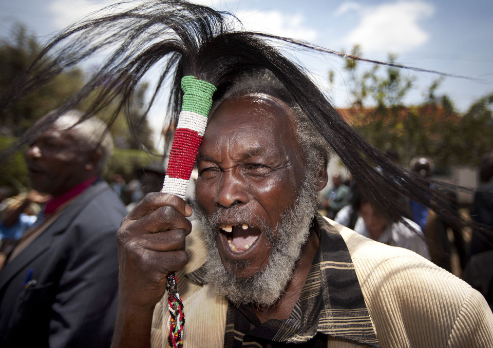 Lawrence Mathenge, representative of the Mau Mau War Veterans Association, celebrates the announcement of a legal decision in Britain's High Court concerning Mau Mau veterans, while holding a ceremonial whisk, at the offices of the Kenya Human Rights Commission in Nairobi, Kenya Friday, Oct. 5, 2012. Britain's High Court ruled Friday that three Kenyans tortured during the Mau Mau rebellion against British colonial rule can proceed with compensation claims against the British government. (AP Photo/Ben Curtis)