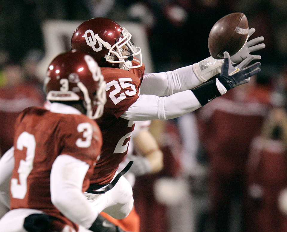 Photo - Oklahoma's D.J. Wolfe (25) intercepts a Nebraska pass in the second quarter of the Big 12 Championship game during the University of Oklahoma Sooners (OU) college football game against the University of Nebraska Cornhuskers (NU) at Arrowhead Stadium, on Saturday, Dec. 2, 2006, in Kansas City, Mo.   By Bryan Terry, The Oklahoman  ORG XMIT: KOD