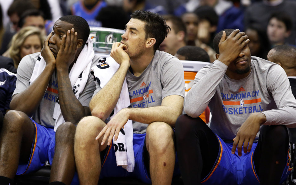 Photo - From left to right, Oklahoma City Thunder center Kendrick Perkins forward Nick Collison and forward Kevin Durant sit on the bench, in the second half of an NBA basketball game against the Washington Wizards, Saturday, Feb. 1, 2014, in Washington. The Wizards won 96-81. (AP Photo/Alex Brandon)