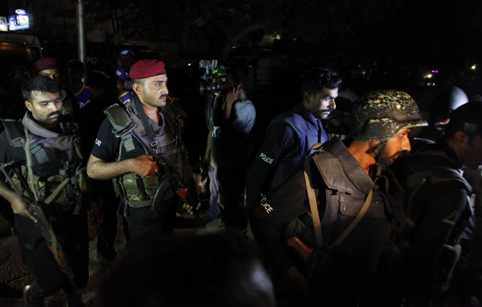 Photo - CORRECTS NUMBER OF PEOPLE KILLED - Pakistani commandos get ready to enter Karachi airport terminal following attacks by unknown gunmen on Sunday night, June 8, 2014, in Pakistan. Gunmen disguised as police guards stormed an airport terminal used for VIPs and cargo in Pakistan's largest city Sunday night, killing at least nine people as explosions echoed into the night, officials said. (AP Photo/Shakil Adil)