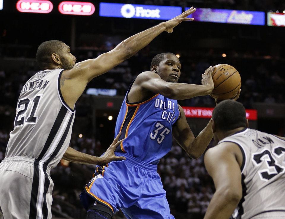Oklahoma Thunder's Kevin Durant (35) looks to pass the ball as San Antonio Spurs' Tim Duncan (21) and Boris Diaw, right, of France, defend during the third quarter of an NBA basketball game, Thursday, Nov. 1, 2012, in San Antonio. (AP Photo/Eric Gay) ORG XMIT: TXEG111