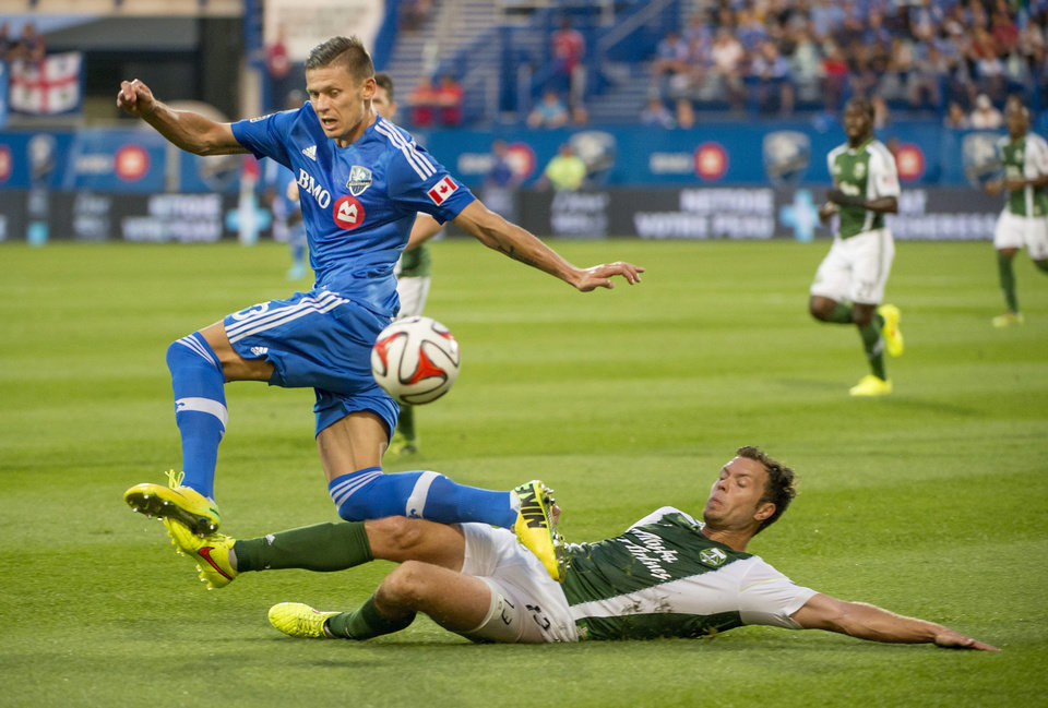 Photo - Portland Timbers' Jack Jewsbury, right, slides into Montreal Impact's Krzysztof Krol during first half MLS action in Montreal on Sunday, July 27, 2014. (AP Photo/The Canadian Press, Peter McCabe)
