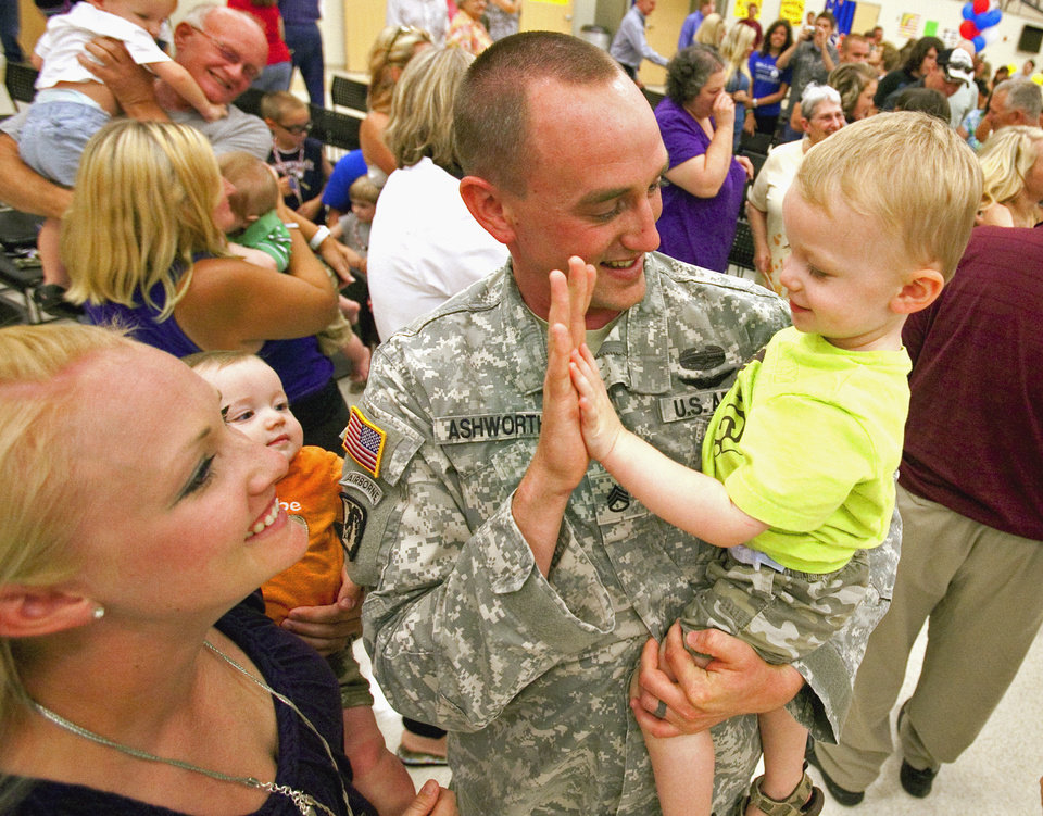 Aaron Ashworth, Tulsa, gives a high five to 20 month old son Stryker as his wife Rosie holds six-month-old Hunter as he and other soldiers from the 1-245th Airfield Operations Battalion return home on Tuesday, August 16, 2011, in Norman, Okla. after spending eight months in Afghanistan.  Ashworth was home for 15 days to witness the birth of his youngest in February.