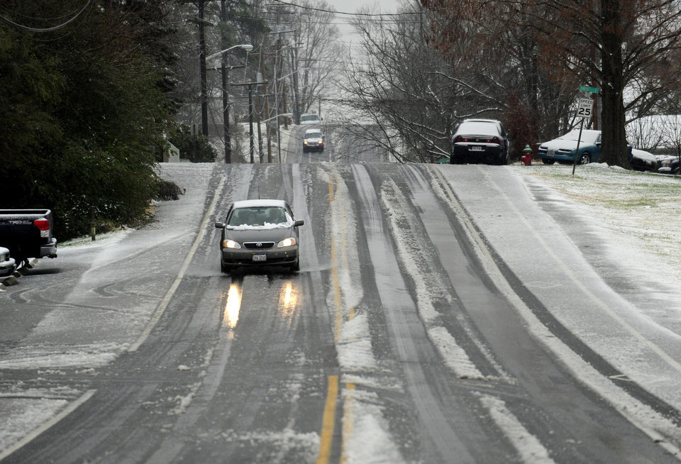 Cars navigate a slushy S. East Street near Yowell Meadow park in the town of Culpeper, Va. An overnight storm brought rain, snow and ice to the Culpeper area on Wednesday, Dec. 26 2012. (AP Photo/The Free Lance-Star, Reza A. Marvashti)