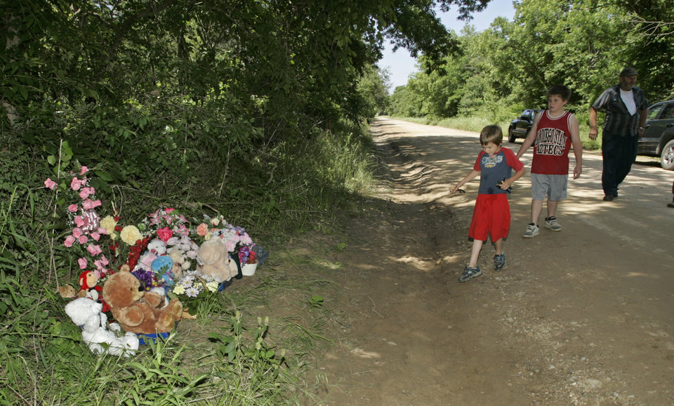 Photo - Devon Padgett, left, 7, Dakota Padgett, center, 10, and their father, Ross Padgett, walk towards a memorial on the side of the road for Skyla Whitaker and Taylor Paschal-Placker, Wednesday, June 11, 2008. The girls were found murdered Sunday night.  (AP Photo)