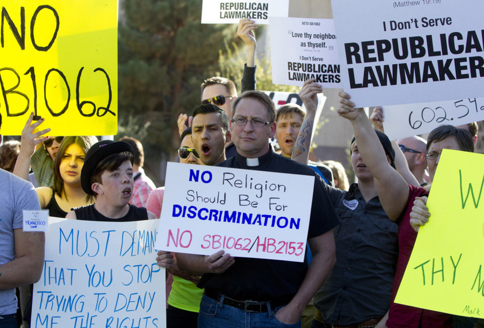 Photo - Opponents of the SB1062, a religious freedom bill, Ryan Ebersole, of Mesa, and Rev. Stephen Govett, of Glendale, urged Gov. Brewer to veto the bill during a protest rally Friday, Feb. 21, 2014, at the state Capitol. (AP Photo/The Arizona Republic, Cheryl Evans)