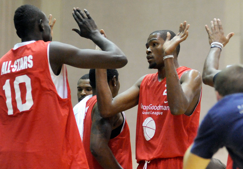 Photo - Kevin Durant, right, of the Oklahoma City Thunder slaps hands with teammates during a charity basketball game hosted by Carmelo Anthony of the New York Knicks on Tuesday, Aug. 30, 2011, at Morgan State University in Baltimore. (AP Photo/Steve Ruark) ORG XMIT: MDSR104