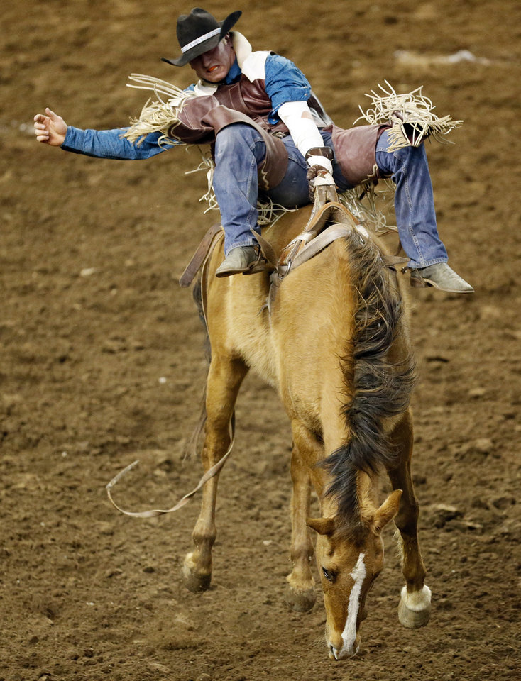 Photo - Danian Nutt of St. Tite, Quebec, competes in bareback bronc during the International Finals Rodeo (IFR 44) at the Jim Norick Arena at State Fair Park in Oklahoma City, Sunday, Jan. 19, 2014. Photo by Nate Billings, The Oklahoman