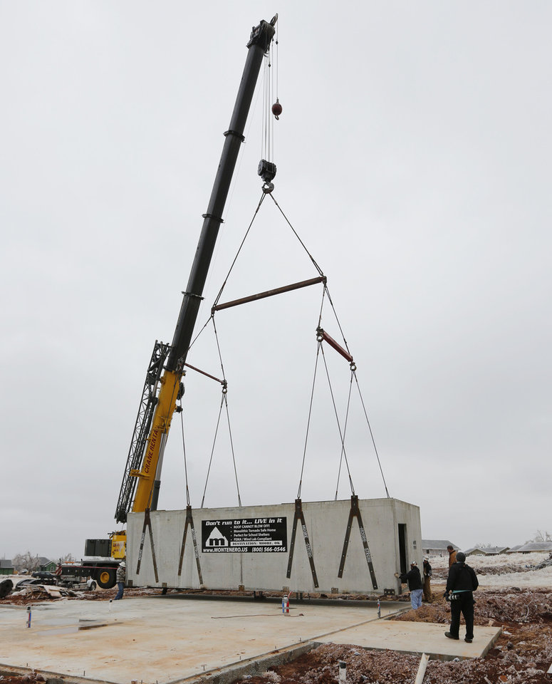 Photo - Workers lower a monolithic safe space for a tornado-resistant house that builder Jay London is building in Moore.  Steve Gooch - The Oklahoman