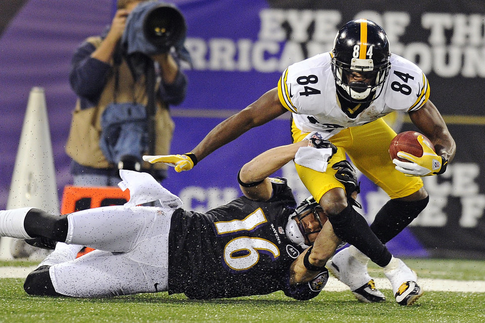 Photo - Baltimore Ravens' David Reed (16) pulls Pittsburgh Steelers wide receiver Antonio Brown to the ground during the first half of an NFL football game in Baltimore, Sunday, Dec. 2, 2012. (AP Photo/Nick Wass)
