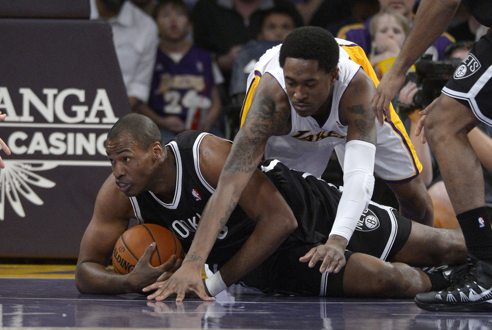 Photo - Brooklyn Nets center Jason Collins, left, battles for a loose ball with Los Angeles Lakers guard MarShon Brooks during the first half of an NBA basketball an NBA basketball game, Sunday, Feb. 23, 2014, in Los Angeles. (AP Photo/Mark J. Terrill)
