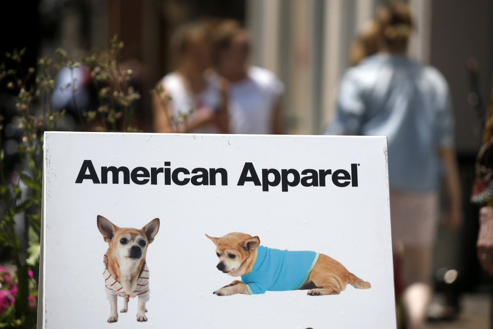 Photo -  Passers-by walk past a sandwich-board sign advertising dog fashions in front of the American Apparel store in the Shadyside neighborhood of Pittsburgh on Wednesday. American Apparel Inc. said has reached a preliminary deal with investment firm Standard General to receive $25 million in financing to bolster the clothing chain's finances, a person close to the negotiations said Wednesday. AP PHOTO   Keith Srakocic