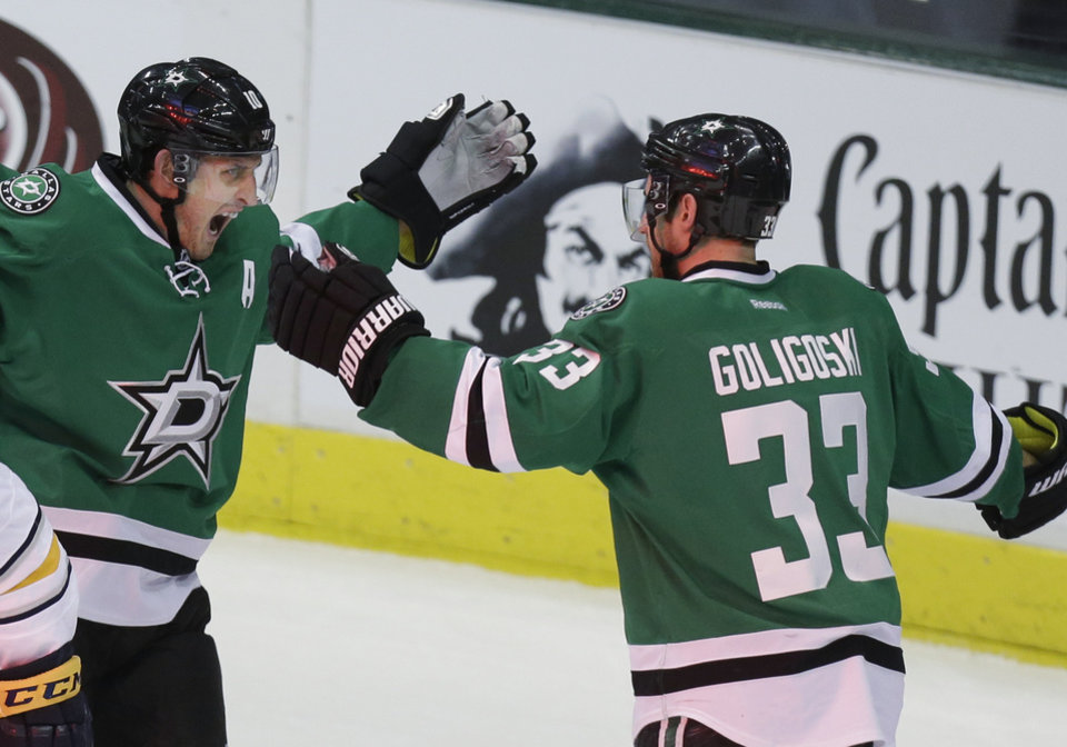 Photo - Dallas Stars defenseman Alex Goligoski (33) celebrates his goal with teammate Shawn Horcoff during the second period of an NHL hockey game against the Buffalo Sabres Monday, March 3, 2014, in Dallas. (AP Photo/LM Otero)
