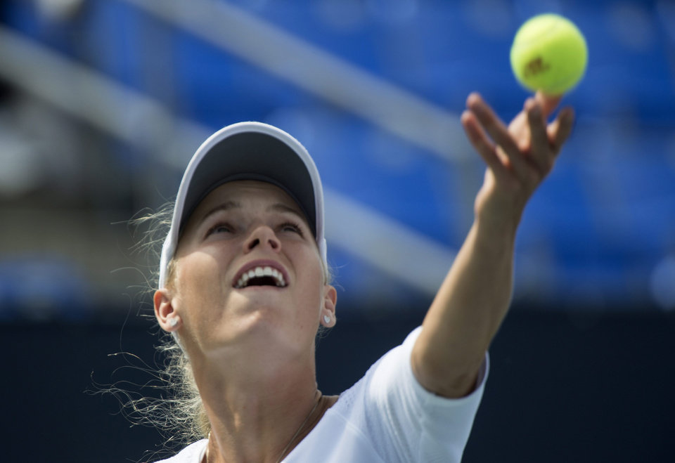 Photo - Caroline Wozniacki, from Denmark, serves to Shelby Rogers during the round of sixteen at the Rogers Cup tennis tournament Thursday, Aug. 7, 2014 in Montreal. (AP Photo/The Canadian Press, Paul Chiasson)
