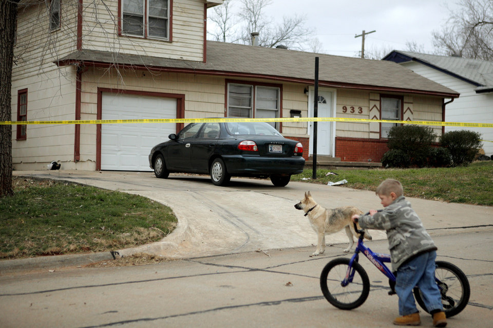 Photo - A neighborhood boy pushes his bike Wednesday near a home where a woman was found dead in Midwest City. Photo by Bryan Terry, The Oklahoman