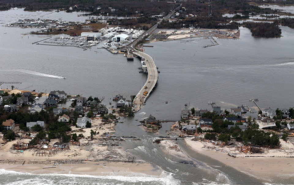 Photo - FILE - This Oct. 31, 2012 file aerial photo shows storm damage from Sandy over the Atlantic Coast in Mantoloking, N.J. Climate change is likely to exact enormous costs on U.S. regional economies in the form of lost property, reduced industrial output and more deaths, according to a report backed by a trio of men with vast business experience that was released on Tuesday, June 24, 2014. (AP Photo/Doug Mills, Pool, File)