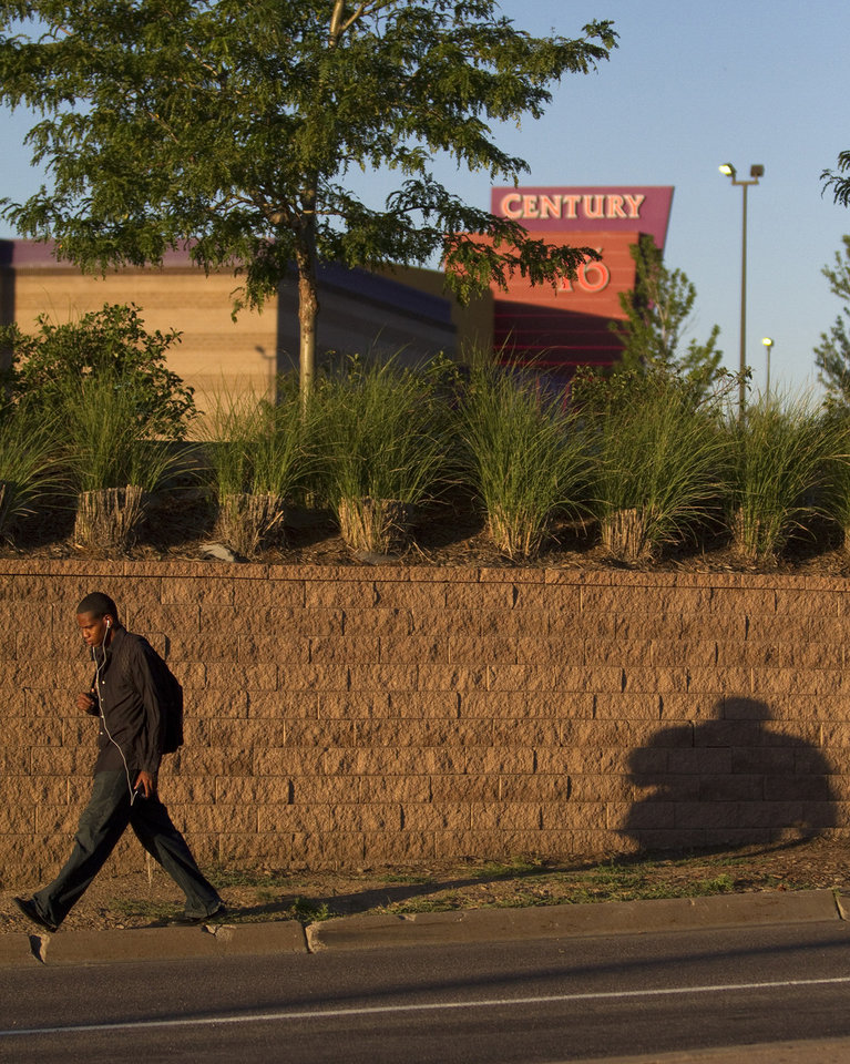 Photo -   A man walks by the Century Theater a day after a deadly shooting on Saturday, July 21, 2012 in Aurora, Colo. Twelve people were killed and dozens were injured in the attack early Friday at the packed theater during a showing of the Batman movie,