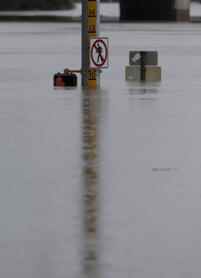 Photo - A flood gage shows waters just under 10 feet at an intersection, Saturday, May 25, 2013, in San Antonio. (AP Photo/Eric Gay)