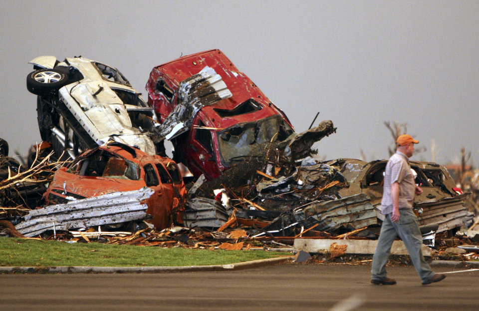 Photo - A man walks past destroyed vehicles in the parking lot of the Joplin Regional Medical Center in Joplin, Mo., Sunday, May 22, 2011. A large tornado moved through much of the city, damaging the hospital and hundreds of homes and businesses. (AP Photo/Mark Schiefelbein) ORG XMIT: MOMS106
