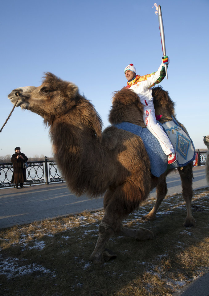 Photo - In this photo taken on Sunday, Jan.  26, 2014 and provided by Olympictorch2014.com, an Olympic torch bearer Dmitry Slaschev, top, rides a camel holding an Olympic torch during the torch relay in  the southern Russian city of Astrakhan.  The relay for the Sochi Winter Games, which began on Oct. 7, 2013 in Moscow, will pass through many cities that showcase the historical, cultural and ethnic richness of Russia. (AP Photo/Olympictorch2014.com)