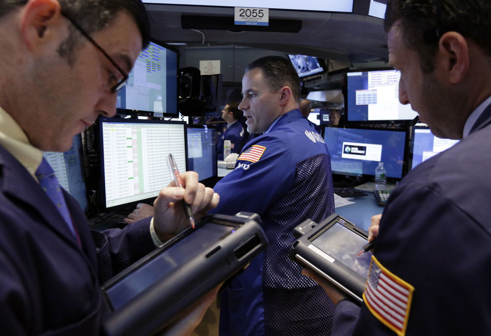 Photo - Traders gather at the post of specialist Jason Hardzewicz, center, on the floor of the New York Stock Exchange Monday, April 28, 2014. Stocks are mostly higher in early trading as traders hope for another blockbuster merger in the health-care industry. (AP Photo/Richard Drew)