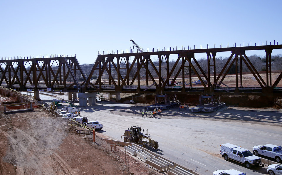 Photo -  Workers install the new railroad bridge Sunday over Interstate 235 in Oklahoma City. [Photo by Sarah Phipps, The Oklahoman]