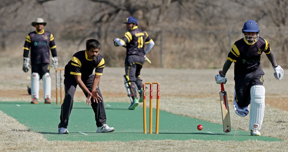Photo -  Batsman Rey Ganadeep, at right, runs as bowler Jagan Patlolla waits for the ball during the Oklahoma City Strikers Cricket Club's first game on its new field at Douglass Park in Oklahoma City, Saturday, March 29, 2014. Photo by Bryan Terry, the Oklahoman