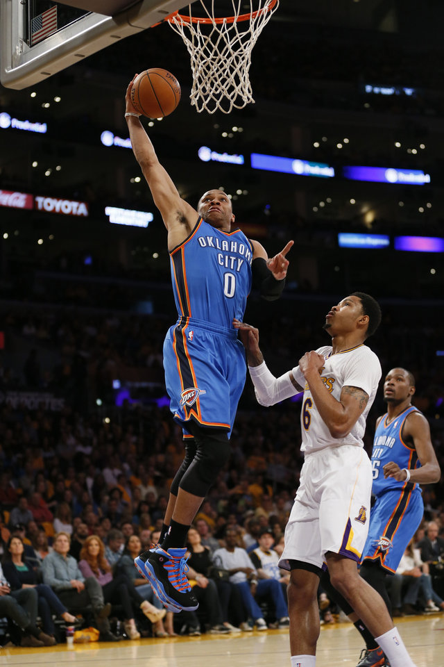 Photo - Oklahoma City Thunder point guard Russell Westbrook, left, goes to the hoop over Los Angeles Lakers shooting guard Kent Bazemore during the first half of an NBA basketball game in Los Angeles, Sunday, March 9, 2014. (AP Photo/Danny Moloshok)