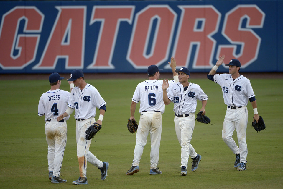 Photo - North Carolina players congratulate each other after defeating Florida 5-2 in an NCAA college baseball regional tournament game in Gainesville, Fla., Saturday, May 31, 2014.(AP Photo/Phelan M. Ebenhack)