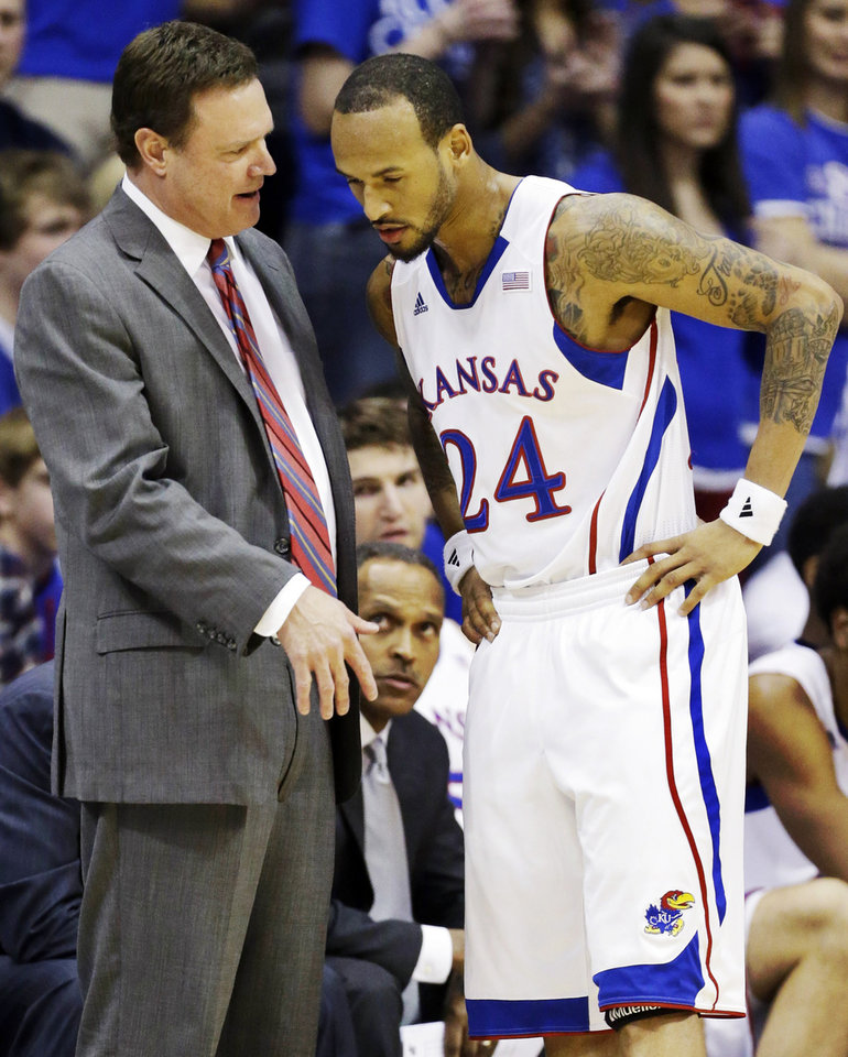 Photo - Kansas head coach Bill Self talks with guard Travis Releford (24) during the first half of an NCAA college basketball game against Oklahoma in Lawrence, Kan., Saturday, Jan. 26, 2013. (AP Photo/Orlin Wagner) ORG XMIT: KSOW104